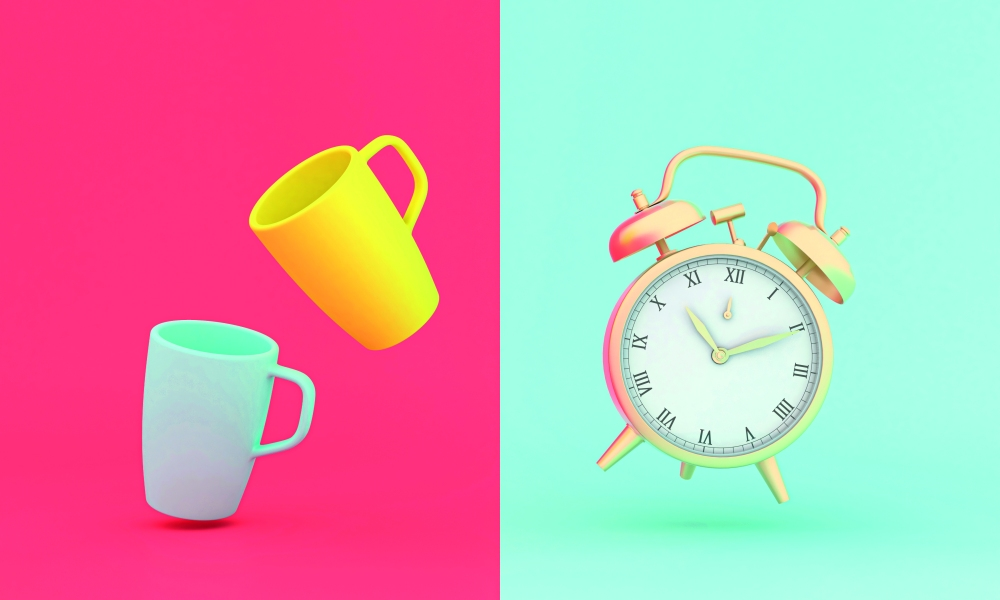 vintage gold alarm clock and stylized cups on two-tone backgroun
