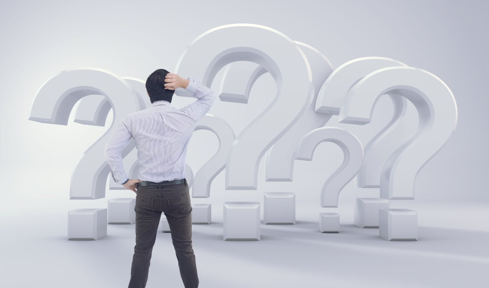 Asian Man Standing In Front of Big Question Mark